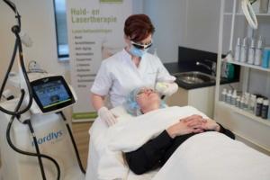 Huidtherapeut behandelt client met laser voor couperose